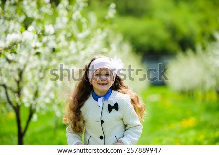 Portrait of Little pretty girl in the green blooming garden