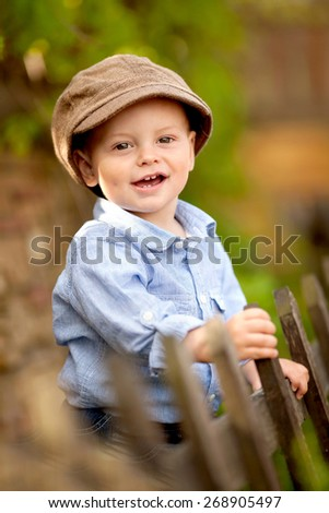 portrait of little smiling boy in the blue shirt and brown cap is standing near the wooden fence in the garden