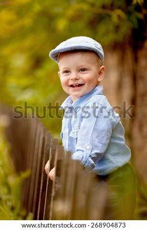 portrait of little smiling boy in the blue shirt and  cap is standing near the wooden fence in the garden