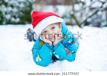 Portrait of little toddler boy three years old santa hat in winter with snow
