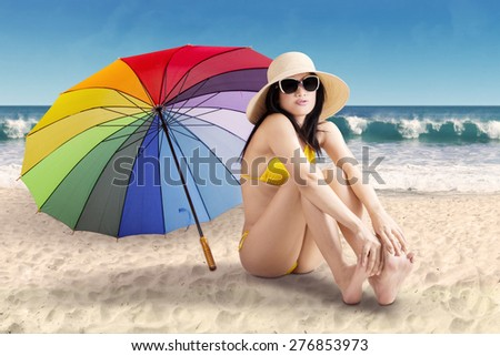Portrait of lovely woman sitting on the coast with a colorful umbrella while wearing sunglasses and hat