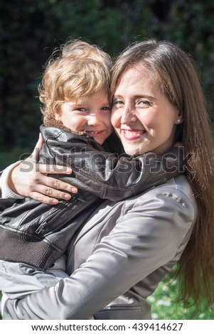 Portrait of loving mother and son embracing in nature and enjoying a day together.