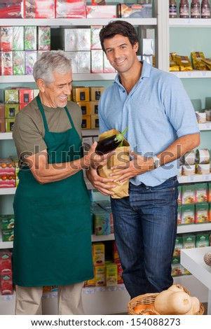 Portrait of male customer with salesman putting vegetable in paper bag