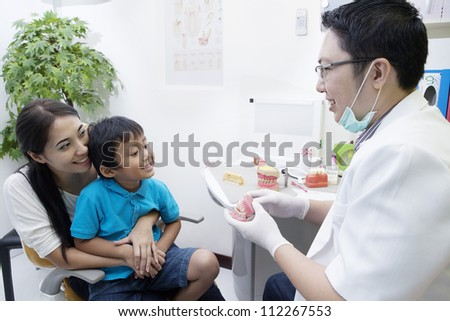 Portrait of male dentist show a sample of braces to his patient at office
