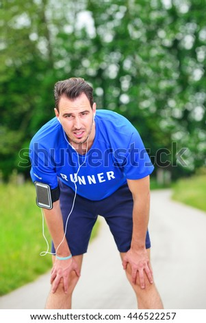 Portrait Of Male Jogger Standing In Field While Listening Music.