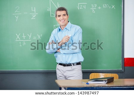 Portrait of male teacher standing arms crossed against board in classroom