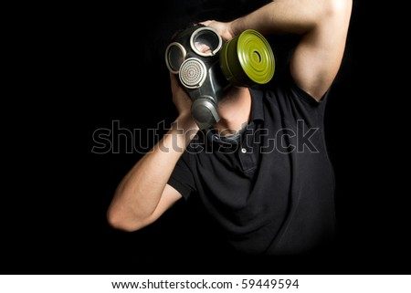 Portrait of man wearing a gas mask on black background