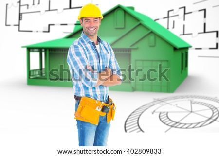 Portrait of manual worker standing arms crossed against house in grey with architect plans
