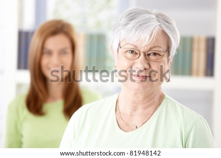 Portrait of mature woman smiling, daughter standing at background.?