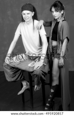 Portrait of men and women have dreadlocks, hippie style. Modern young couple is wearing trendy clothes, on a gray background.