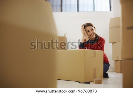 Portrait of mid adult happy woman moving with boxes at new apartment and looking at camera. Copy space