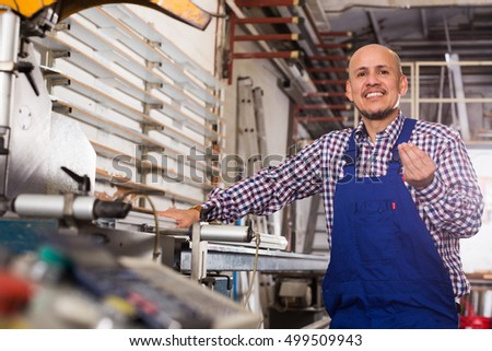 Portrait of middle age guy at professional lathe in plant