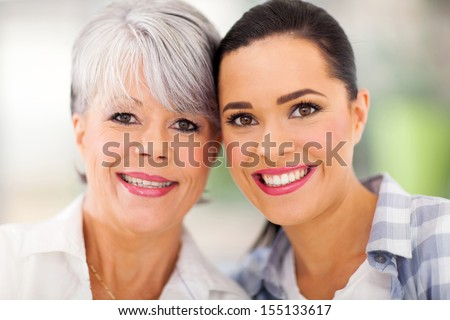 portrait of middle aged mother and young daughter at home