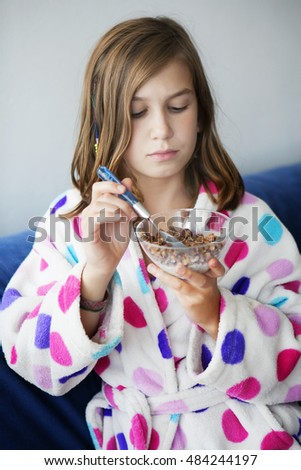 Portrait of moody young girl eating porridge at morning
