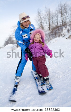 Portrait of mother holding cute girl while skiing