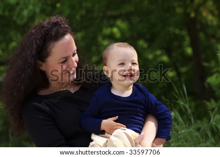 Portrait of mother holding her smiling son in hands