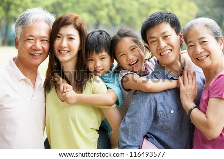 Portrait Of Multi-Generation Chinese Family Relaxing In Park Together