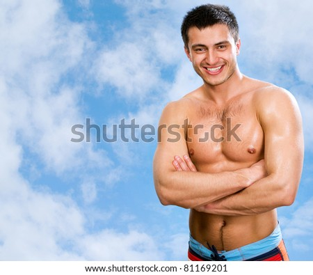 Portrait of muscular man against the blue sky