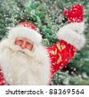 Portrait of natural Santa Claus standing at Christmas Tree outdoors in winter and welcoming you with open hands - stock photo