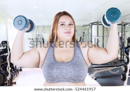 Portrait of obese woman lifting dumbbells while standing at the fitness center