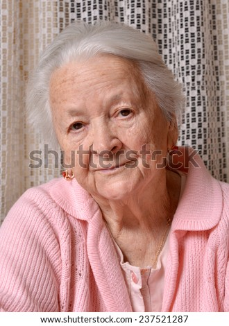 Portrait of old sad woman at home
