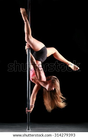 portrait of one young women doing exercises on the pylon on a black background Studio
