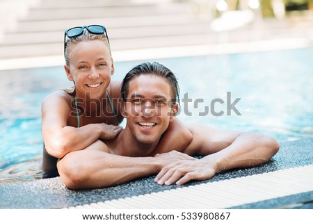 Portrait of passionate young love couple in swimming pool at resort