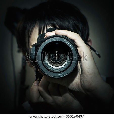 Portrait of photographer with camera in hand closeup
