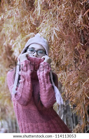 Portrait of playful woman with winter sweater on autumn day