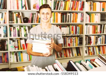 Portrait of positive teenager boy with book pile in shop