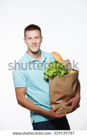 Portrait of positive young male chef in white uniform. Head-cook holding package with fresh food. Standing against grey background