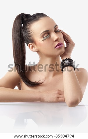 portrait of pretty and sensual brunette with hair pony  tail and creative make up with long eyelashes posing