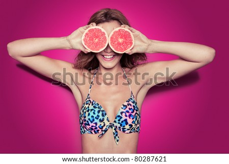 portrait of pretty bikini woman with grapefruit against pink background