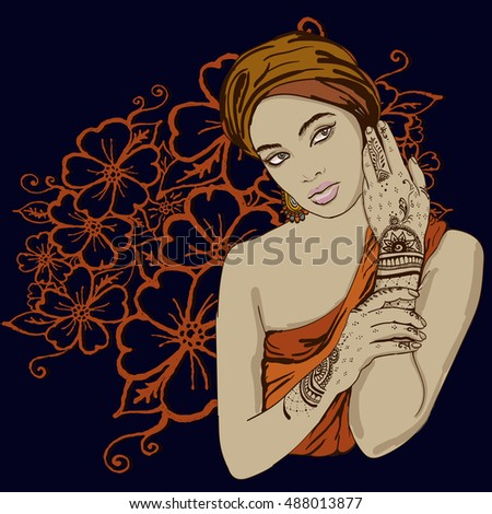 portrait of pretty indian etnic Girl in traditional turban, with henna tatoo mehendy on her hand. copy spase.