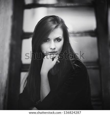 Portrait of pretty young female sitting on stairs, black and white