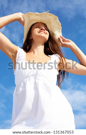 Portrait of pretty young lady in white dress and hat against blue sky