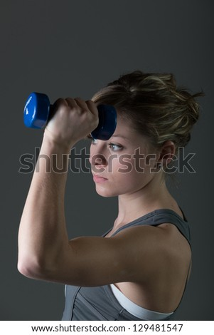 Portrait of pretty, young woman lifting dumbbells during workout