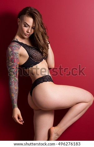 Portrait of pretty young woman with tattooed hand and stylish haircut against red wall.