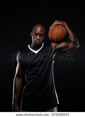 Portrait of professional basketball player holding the ball on his shoulders against black background.