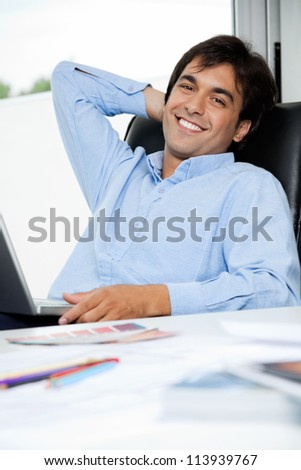 Portrait of relaxed young male interior designer with laptop sitting in office chair