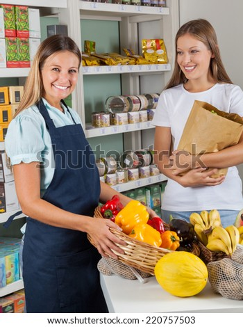 Portrait of saleswoman holding vegetable basket with female customer in supermarket