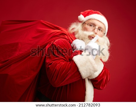Portrait of Santa Claus with huge red sack keeping forefinger by his mouth