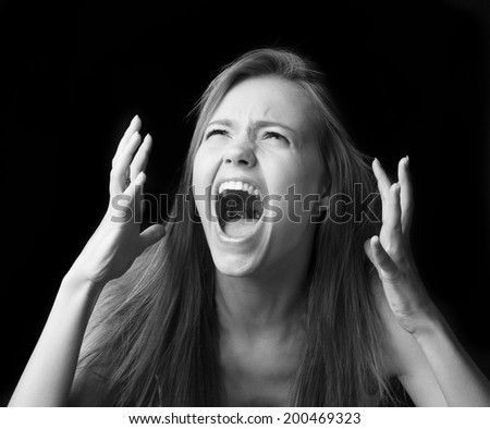 Portrait of screaming girl on black background