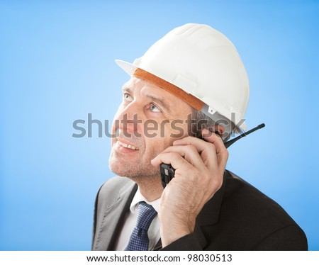 Portrait of senior architect talking on walkie-talkie at construction