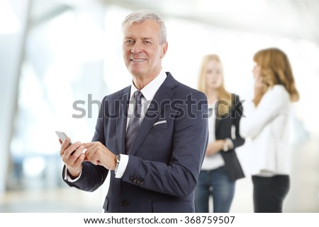 Portrait of senior businessman holding in hands cellular phone at standing at office while business people consulting at background.