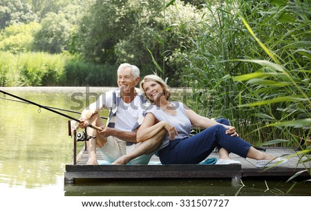 Portrait of senior couple sitting at pier while fishing at lakeside.