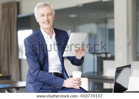 Portrait of senior professional man using digital tablet and drinking coffee in boardroom.
