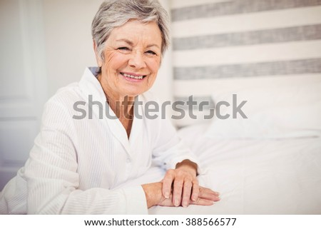 Portrait of senior woman smiling while sitting on bed