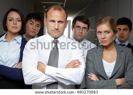 Portrait of serious business team standing with arms crossed