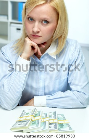 Portrait of serious woman with banknotes lying in front of her on table